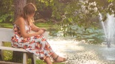 city : side view blond girl in colorful frock sits on bench near pond with fountain in park smoothes long hair checks iphone Stock Footage