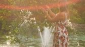 backlit : at backlight backside view blond girl in colorful frock takes photo of pond fountain in park from different places Stock Footage
