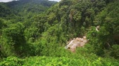 wood : panorama of tropical green hills with distant waterfall and grass on foreground against blue sky Stock Footage