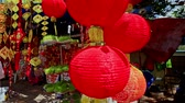 brilho : NHA TRANG, KHANH HOA  VIETNAM - JANUARY 26, 2017: Wind shakes hung up large nice red Chinese lanterns on street market in city before Vietnamese new year TET on January 26 in Nha Trang