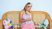 tart : young blond woman in artificial flower garland sits in wooden armchair among toys and holds in arms doll