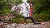 tart : slim athletic girl with pigtail does yoga on rocky ground on knee with hands over head against powerful waterfall
