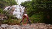tart : cute girl with ponytail bends to bare foot in yoga pose on rock by waterfall streaming from cliffs