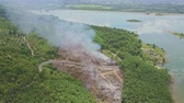 trees : flycam shows a great panorama of highland with fires in jungle meandering mountain road and pictorial lake