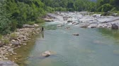 margem do rio : drone view guy stands on rocky bank and throws net in shallow river by rapids against tropical highland