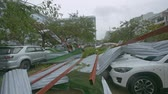 consequence : NHA TRANG  VIETNAM - NOVEMBER 05 2017: Broken roofs from buildings lie on modern cars among felled trees as result of violent hurricane on November 05 in Nha Trang