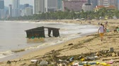 consequence : floating house remainder at sea shore after devastating typhoon against impressive cityscape