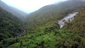 tableland : drone flies from gorge with rocky river running between forestry hills to pictorial tableland with waterfall