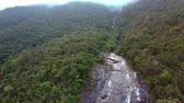 long distance : drone rises above stone tableland with waterfall against boundless misty jungle and hazy distance