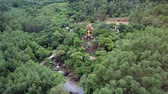 vysočina : drone shows gold standing Buddha statue at ancient Buddhists temple near road and river among tropical forest