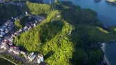 вьетнамский : flycam shows modern resort city between green sunny hills on island in beautiful ocean bay at sunset