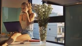 krizantem : beautiful blond girl with ponytail sits on wide windowsill near white chrysanthemums drinks Stok Video