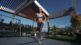 çatı katı : pretty young woman with plaits in open top and leggings squats in fitness pose on decorative roof lounge under blue sky Stok Video