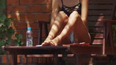 coxa : closeup slim girl in bikini smears legs and thighs with sunscreen on wooden chaise lounge bottle of water on foreground Stock Footage