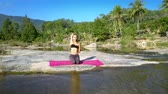 river rapids : lady in top relaxes in yoga pose among river