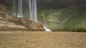 pedregulhos : huge brown boulders against powerful waterfall Stock Footage
