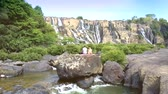 погоня : tourist couple sits on rock watch waterfall