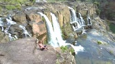 rabo de cavalo : girl barefoot takes seat on rock at waterfall level
