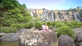 rapid : couple sits on rock among river rapids by waterfall Stock Footage
