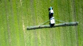vertical growth : close vertical view tractor trailed sprayer drives on field Stock Footage