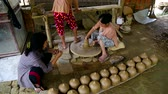 terracota : women work with large wheel and talk in pottery workshop