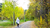 tyumen : girl in white hoodie jacket does Nordic walking in park