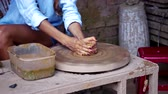 terracota : master starts girl continues making clay pot on potter wheel