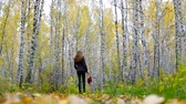 csikk : long haired girl with red handbag walks among gold birches