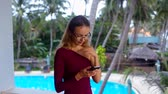 ношение : blonde girl in glasses texts on phone against swimming pool Стоковые видеозаписи