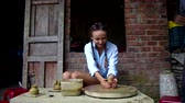 терракота : joyful girl wets hands and makes clay pot on wheel at lesson