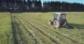 tyumen : farmer operates tractor mowing grass for hay in countryside