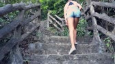 backside view woman in shorts goes up stone stairs on hill