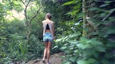backside view girl goes down stone steps in jungle