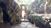backside girl walks through gate in stone arch from cave