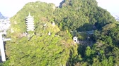 aerial zoom out wonderful old buddhist temple with traditional pagoda on single green hill surrounded by city