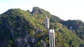 modern high elevator to beautiful pagoda among deep rainforest on hill near city under clear blue sky 動画素材
