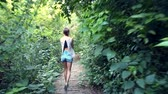 backside view young woman in denim shorts walks along stone track across deep tropical jungle 動画素材