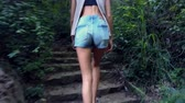 šortky : backside view long haired girl in blouse and denim shorts goes up old abandoned stone steps in thick forest Dostupné videozáznamy
