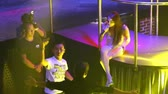 NHA TRANGVIETNAM - JULY 12 2015: Asian girl singer in white sits on stage and sings with guy spectator in popular night club on July 12 in Nha Trang