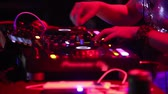 NHA TRANGVIETNAM - JULY 25 2015: Closeup girl dj hands move levers on music mixer console playing modern music under flashing lights in nightclub on July 25 in Nha Trang