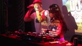 discotheque : NHA TRANGVIETNAM - JULY 25 2015: Smart girl dj in silver top and guy in t-shirt nightclub party host dance by mixer console against screen on July 25 in Nha Trang