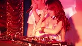 discotheque : NHA TRANGVIETNAM - JULY 25 2015: Joyful dancing showman and beautiful popular Asian girl dj at console entertain clubbers at night party on July 25 in Nha Trang Stock Footage
