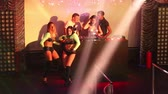 솔직한 : NHA TRANGVIETNAM - JULY 25 2015: Nice girls go-go dancers in frank dresses dance on stage to dj music in colorful projector lights at nightclub party on July 25 in Nha Trang