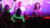 솔직한 : NHA TRANGVIETNAM - JULY 25 2015: Slim girls go-go dancers in frank dresses dance on stage against dj console in colorful projector lights  on July 25 in Nha Trang