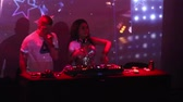 NHA TRANGVIETNAM - JULY 25 2015: Close view joyful dancing showman and girl dj at console entertain clubbers against flashing screen in nightclub  on July 25 in Nha Trang