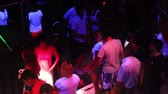 NHA TRANGVIETNAM - JULY 25 2015: Joyful young clubbers dance on club floor near stage under flashing projector lights in popular nightclub on July 25 in Nha Trang
