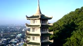 aerial inspiring view brightly lit white upper levels of high buddhist temple pagoda on green hill against city 動画素材