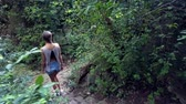 side view girl in denim shorts goes down stone steps and stops to choose path in deep tropical park 動画素材