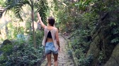 halenka : backside view girl in denim shorts and modern blouse walks along stone path in thick tropical park