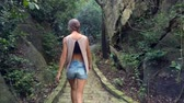 halenka : backside view long haired girl in blouse and shorts walks along old stone track among tropical park